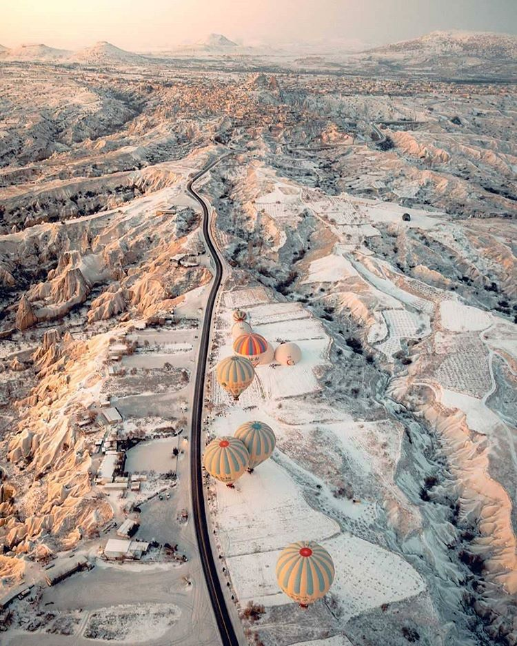 aerial photography of hot air balloons flighing over white cliffs