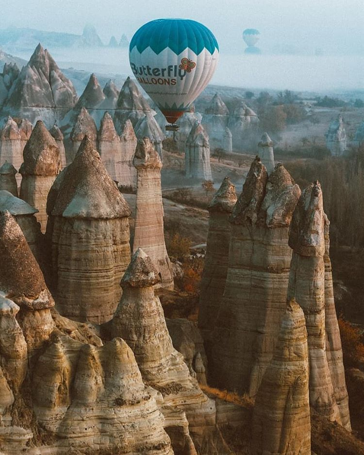 hot air balloon flighing over sharp rock formation