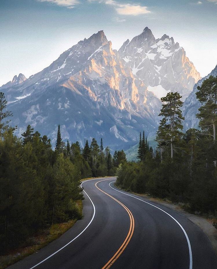 sinuous american road with scenic mountain range behind