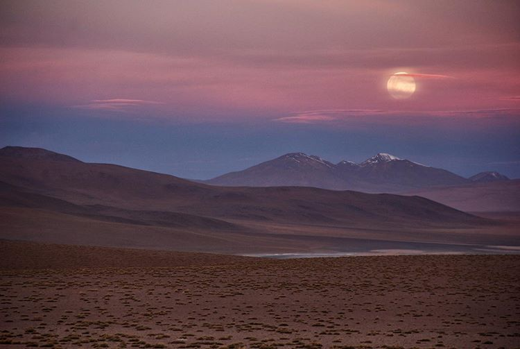 mountains in the background with the moon and desert in the foreground