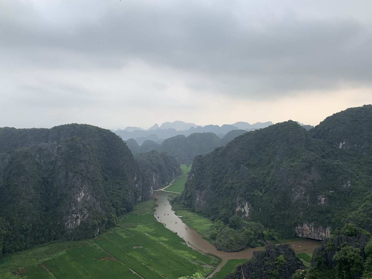aerial photography of muddy river with rice fields and mountains