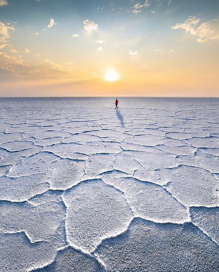 person-walking-on-white-soil-with-sun-setting