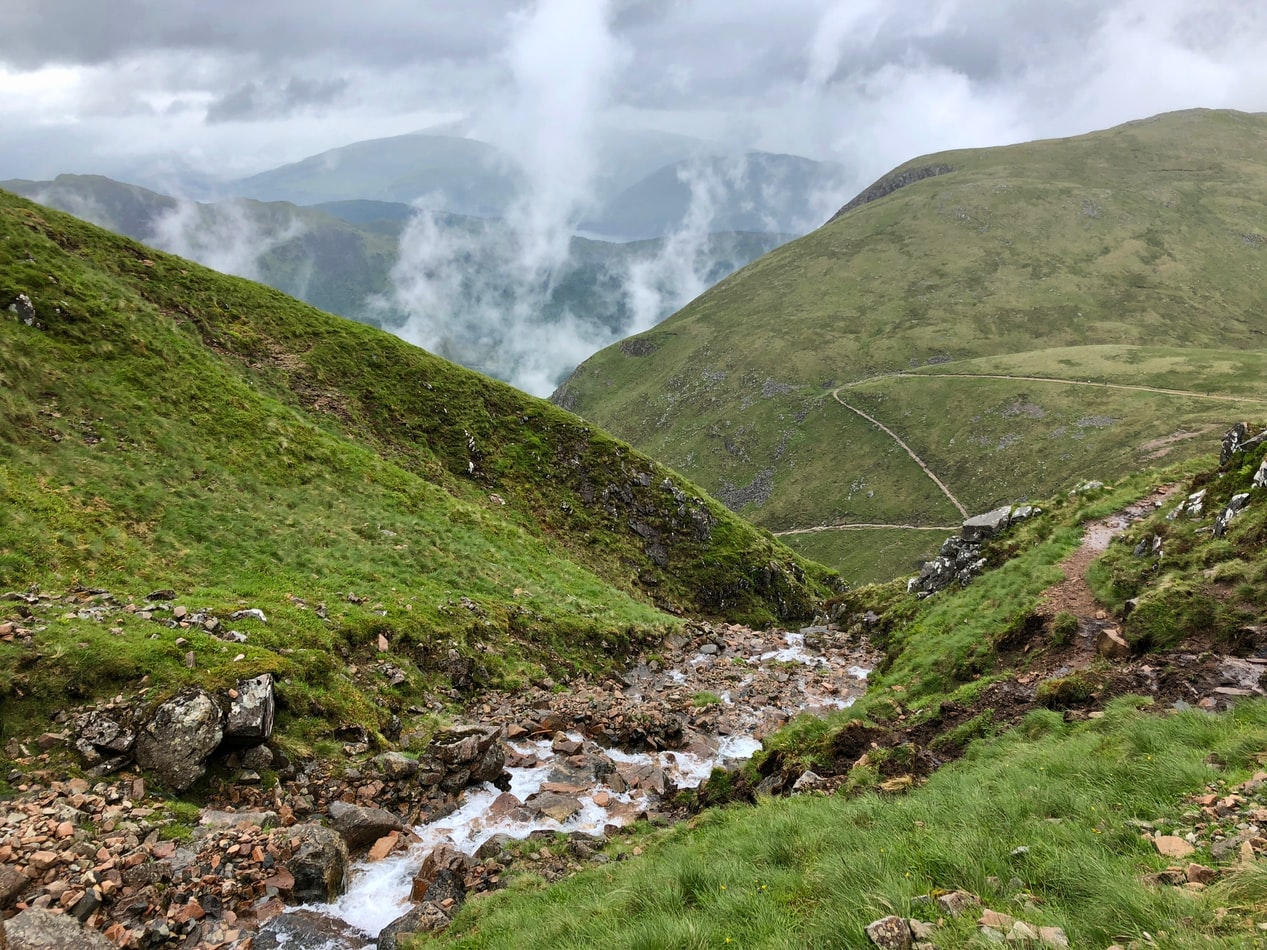 river flowing down a green mountain under cloudy sky photo in ben nevis hikes in europe