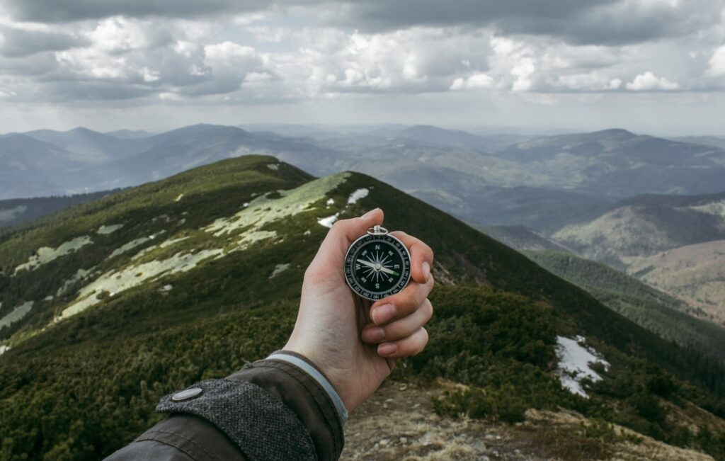 person holding a silver compass with the carpathian mountains in the background
