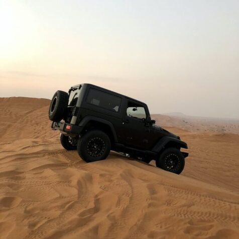black jeep in the desert at day time photo