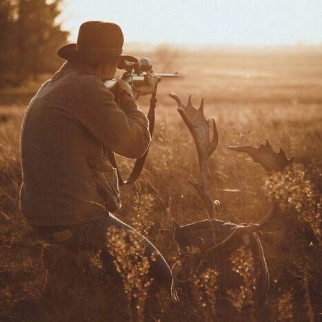 man hunting wearing a hat at sunrise photo