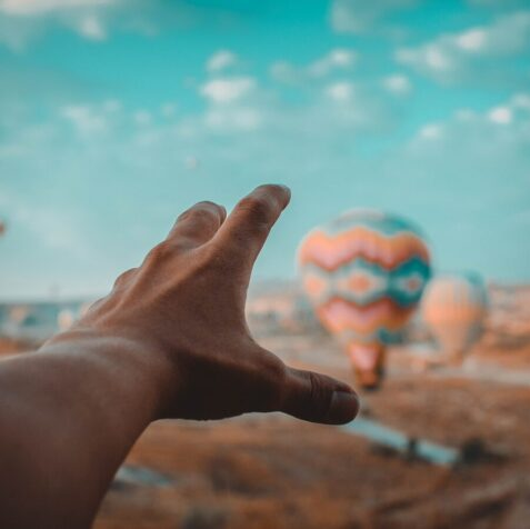 pov of hand about to catch a hot air balloon in cappadocia