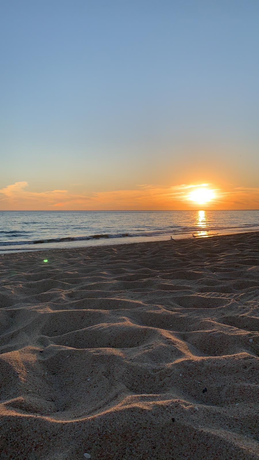 sand in the foreground with sunset for days around faro