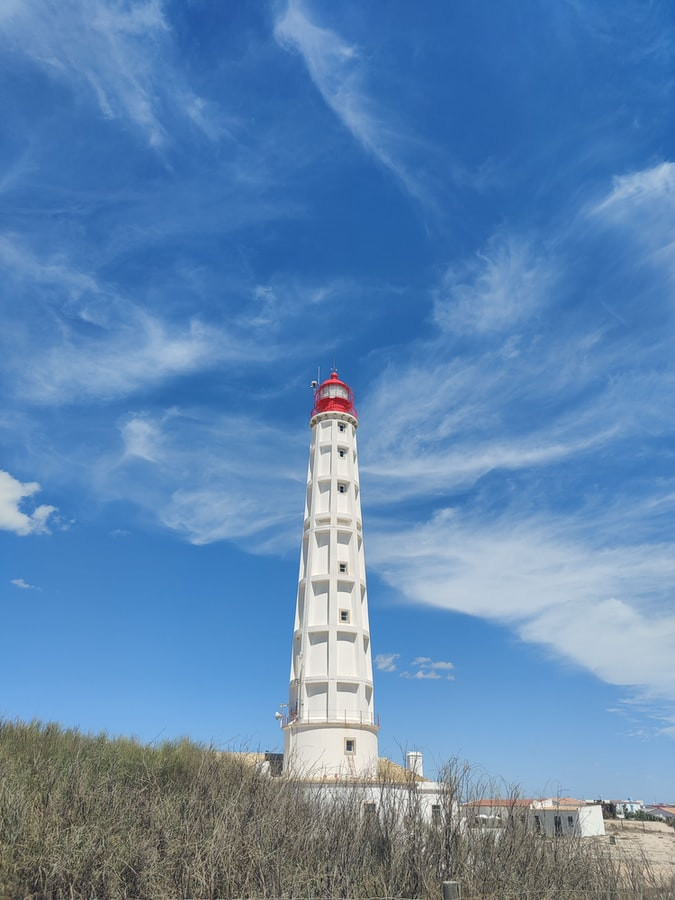 white and red lighthouse under blue sky at day time photo