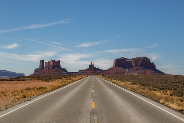 grey concrete road between brown rocks in monument valley