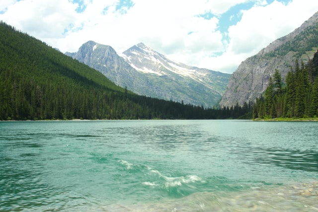 calm body of water near mountains in glacier national park