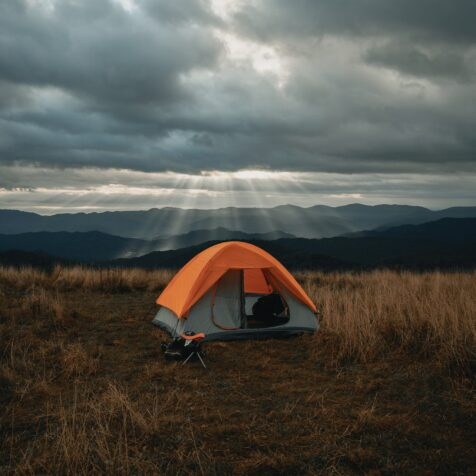set-up grey and orange tent on yellow and brown field under cloudy sky in picos de europa