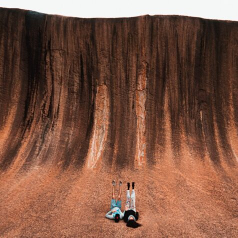 two person lying next to wave rock photo